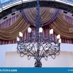 Elegant Wrought Iron Chandelier On The Ceiling Against The Backdrop Of Curtains Stock Image Image Of Folds Decoration 150491381