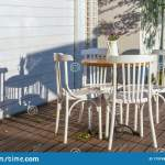 An Empty Table Of An Outdoor Cafe With White Painted Chairs On A Wooden Floor Stock Photo Image Of Eatery Exterior 179748352