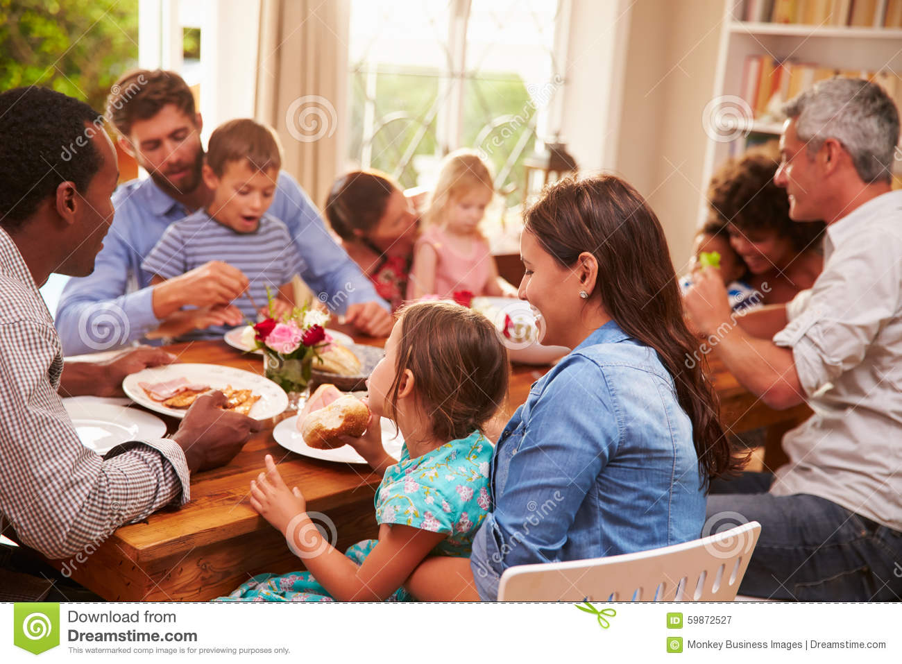 Family And Friends Sitting At A Dining Table Stock Image