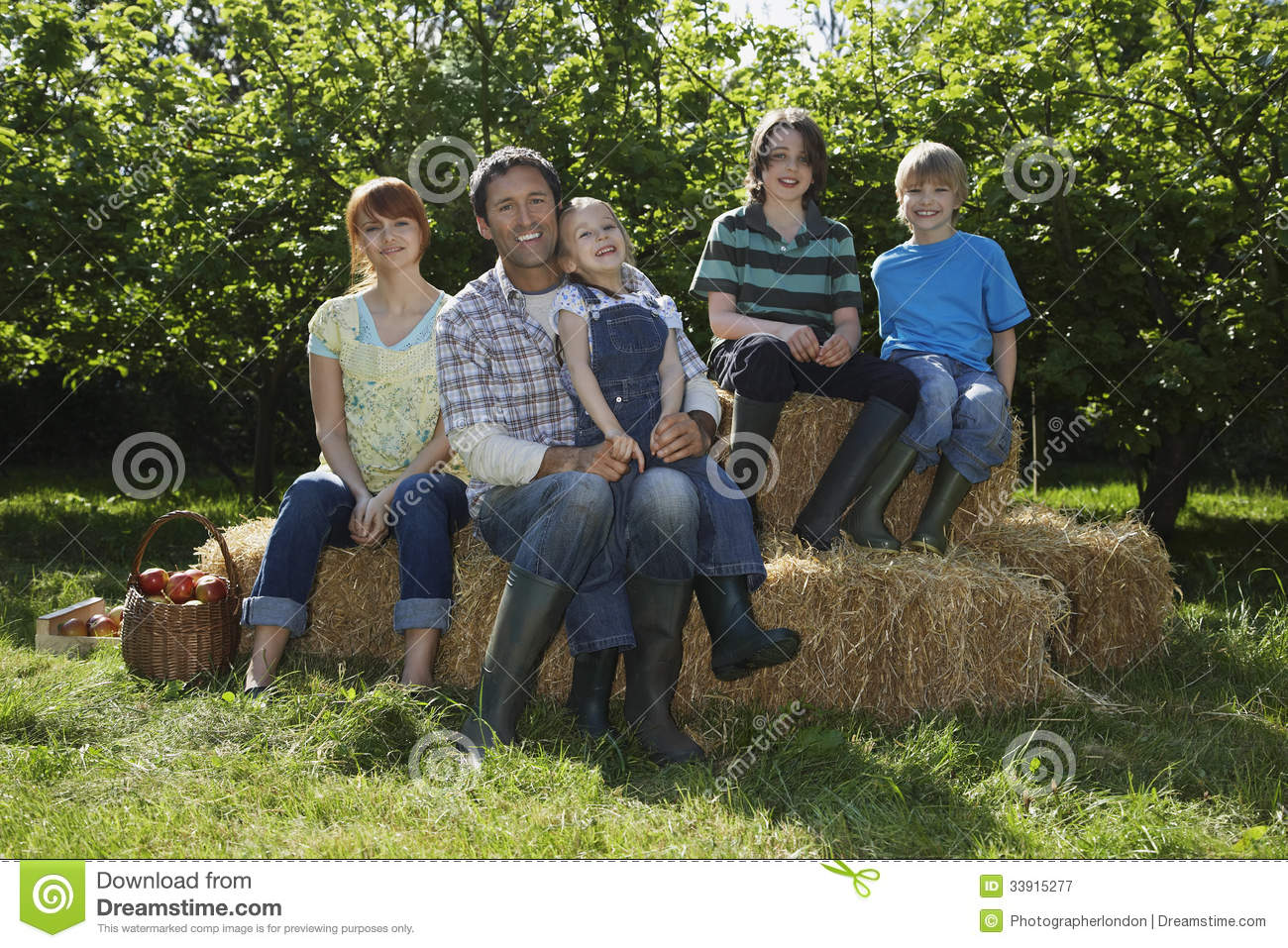 Family Sitting On Hay Bales Near Orchard Royalty Free