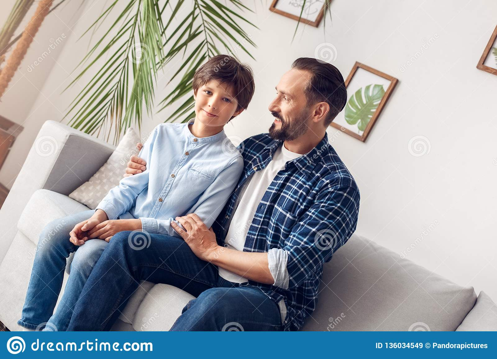 Father And Little Son At Home Sitting On Sofa Dad Talking