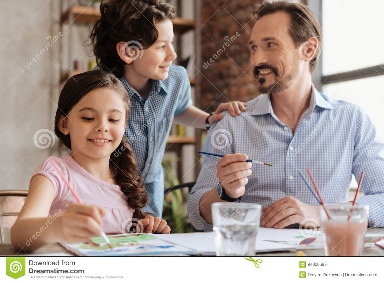 Father And Son Communicating While Daughter Painting Stock