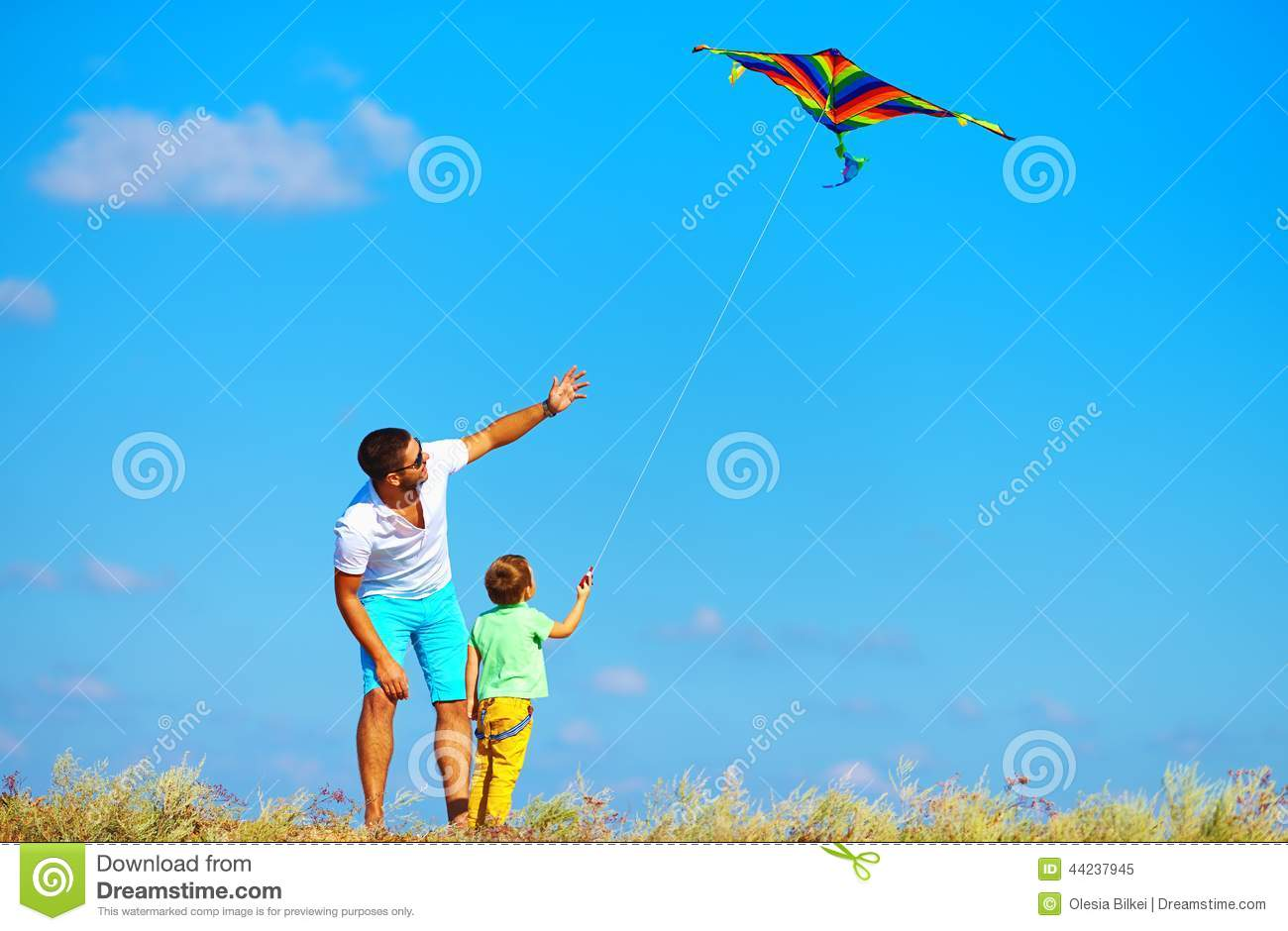 Father And Son Having Fun Playing With Kite Together