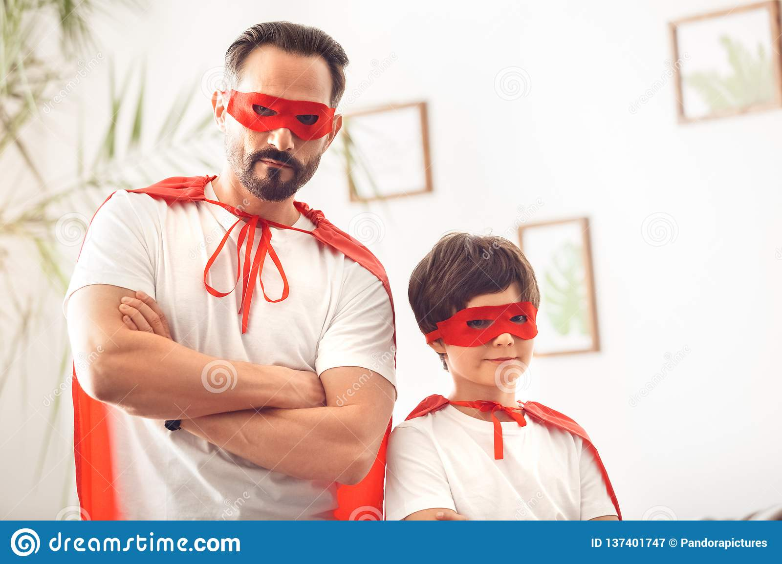 Father And Son In Superheroe Costumes At Home Standing