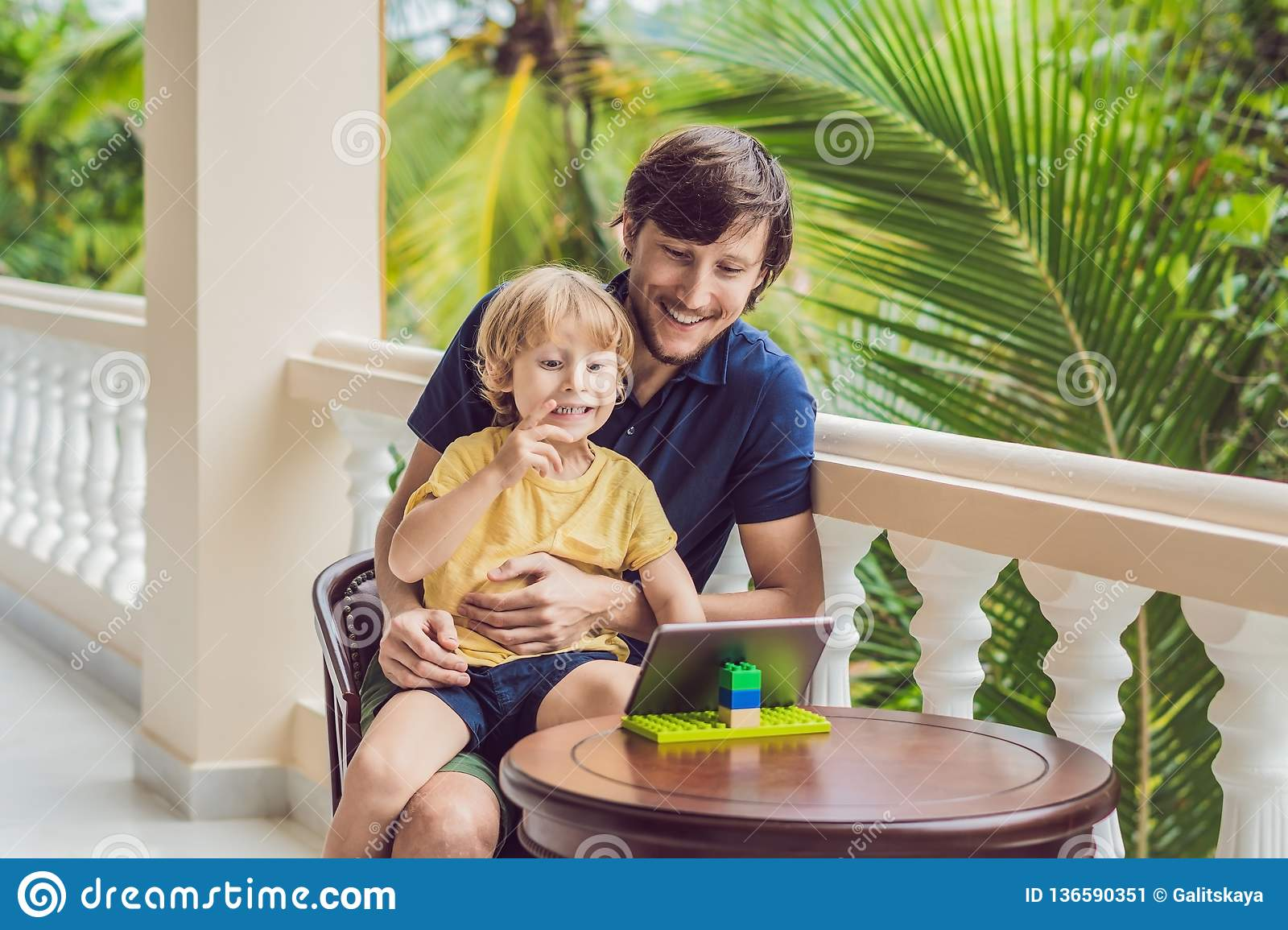Father And Son In Tropics Talking With Friends And Family