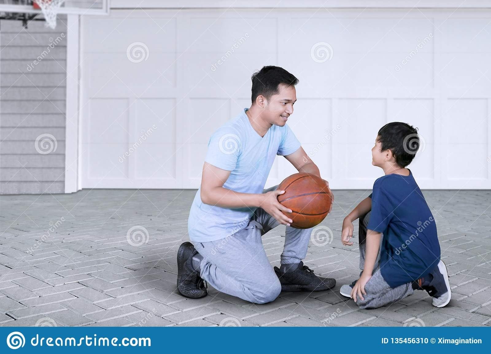 Father Teaching His Son To Play Basketball Stock Photo