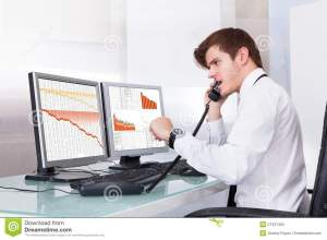 Frustrated Stock Broker Working At Office Stock Photo