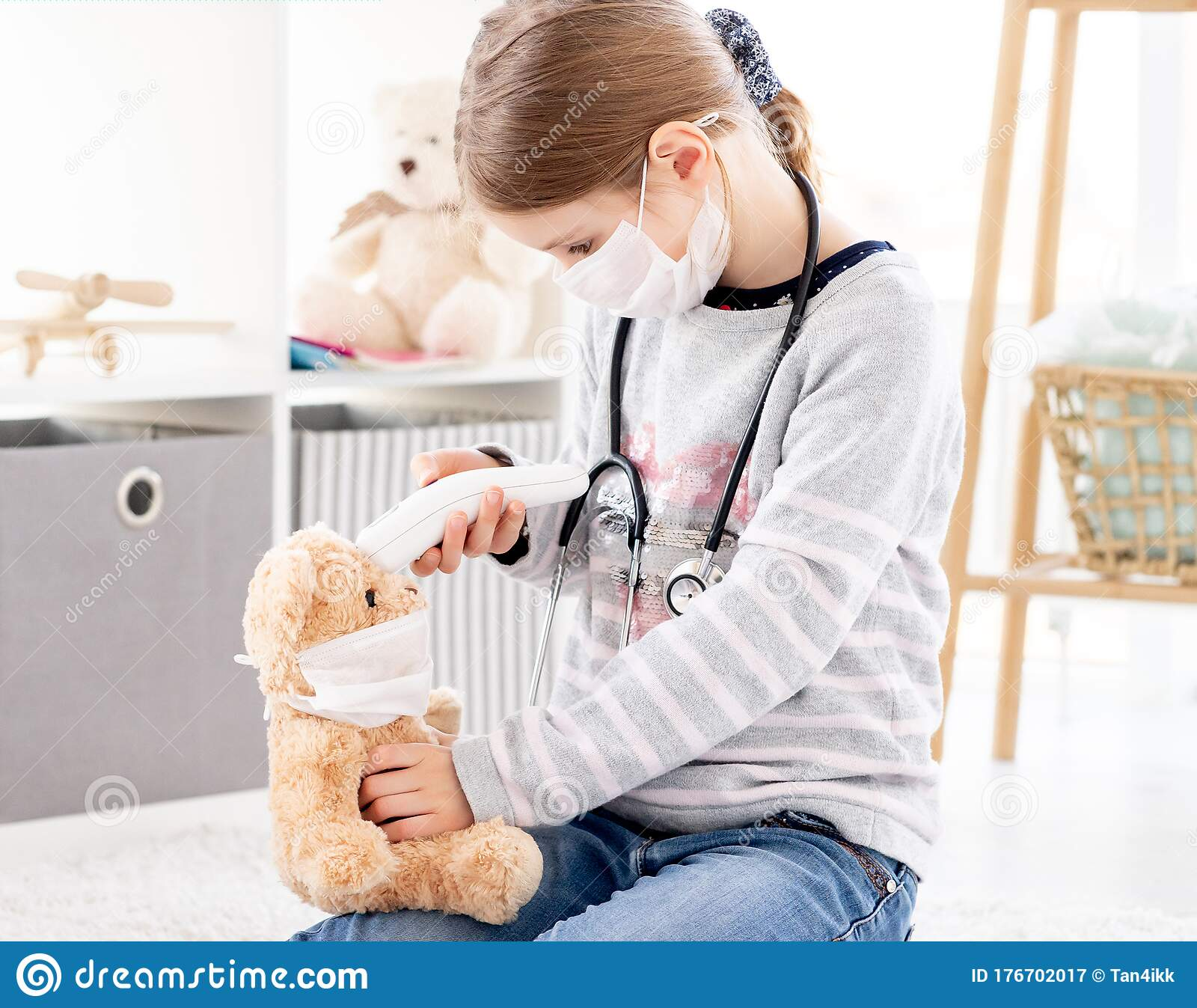 Girl Measuring Teddy Bear Temperature Stock Image