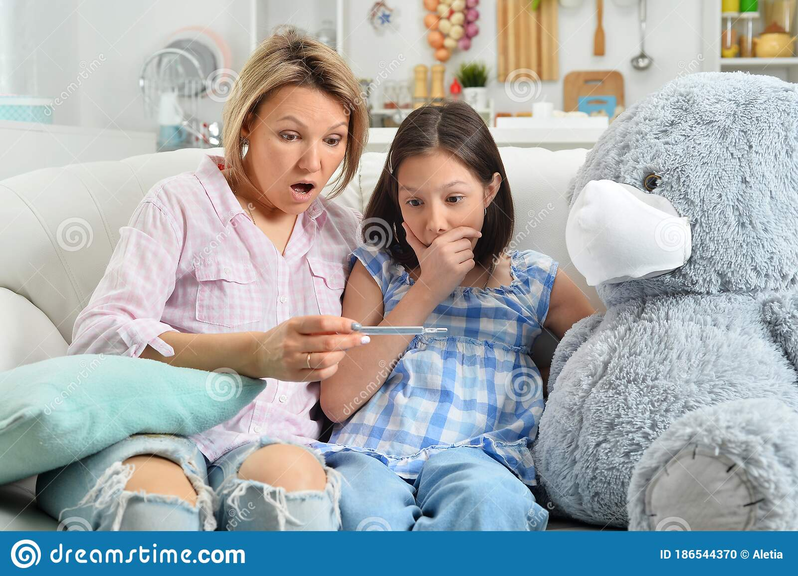 Girl And Mother Playing With Toy Teddy Bear In Facial Mask