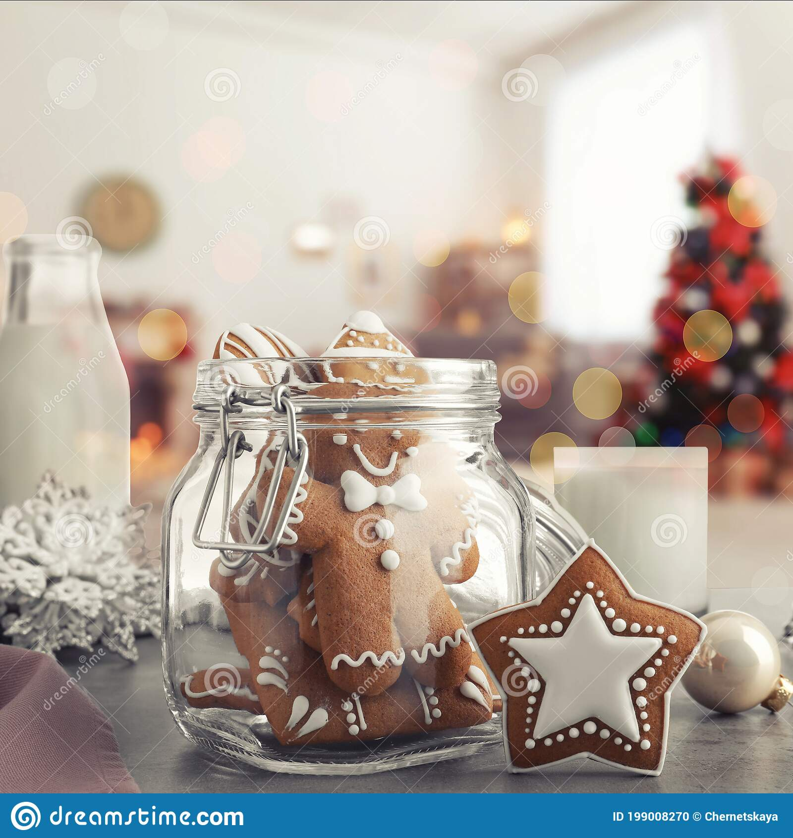 glass jar with christmas cookies milk and ornaments on table in room stock photo image of merry lights 199008270