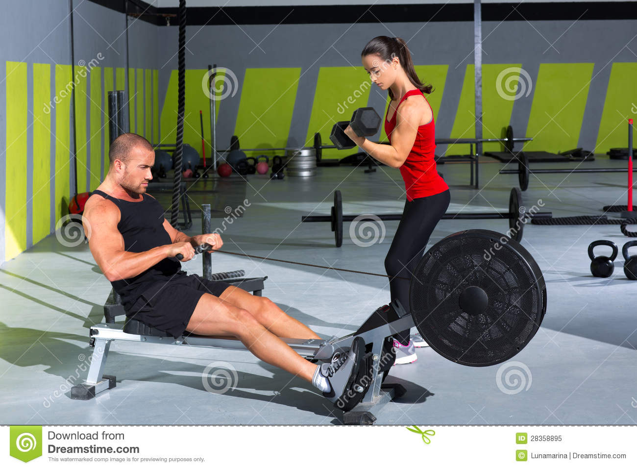 Gym Couple With Dumbbell Weights And Fitness Rower Stock