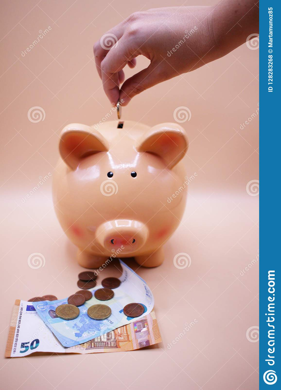 Hand Introducing A Coin Into Piggy Bank With Savings Stock