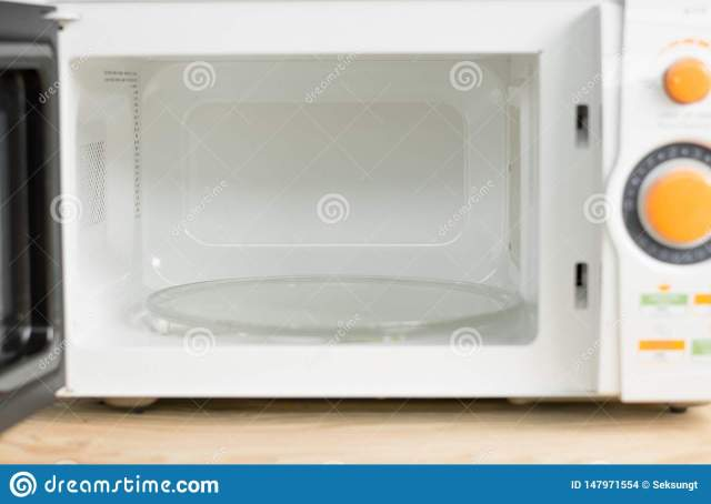 Hand With Microfiber Cleaning Rag Wiping Inside Of Microwave Oven