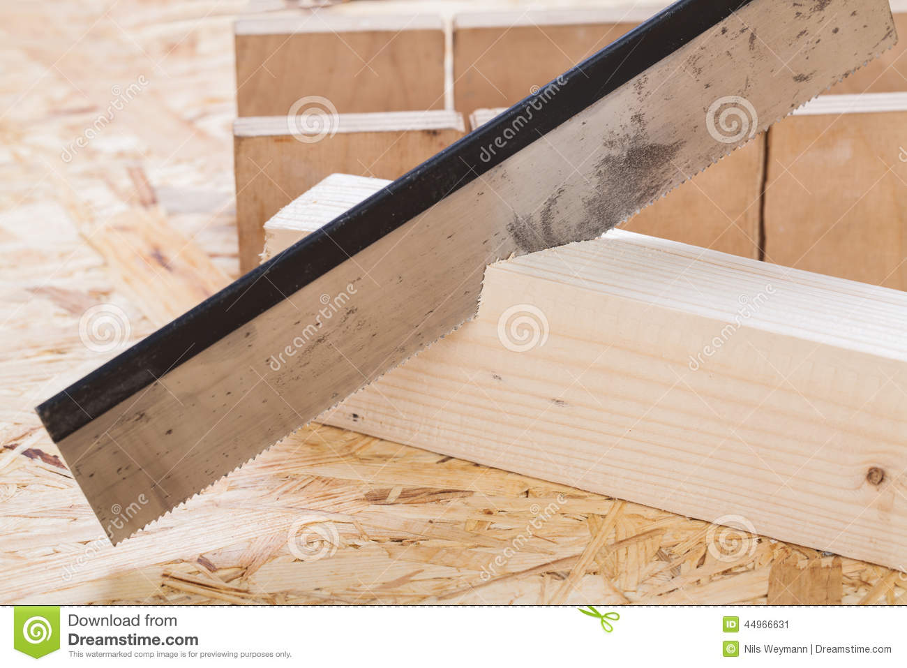 Hand Saw Cutting Through A Beam Of Wood Stock Photo