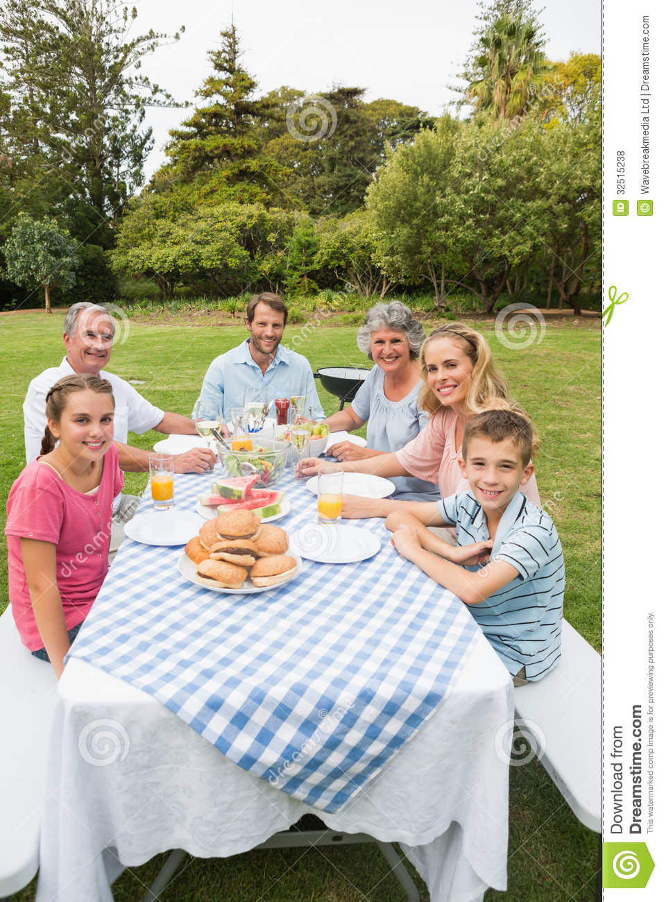 Happy Extended Family Having Dinner Outdoors At Picnic