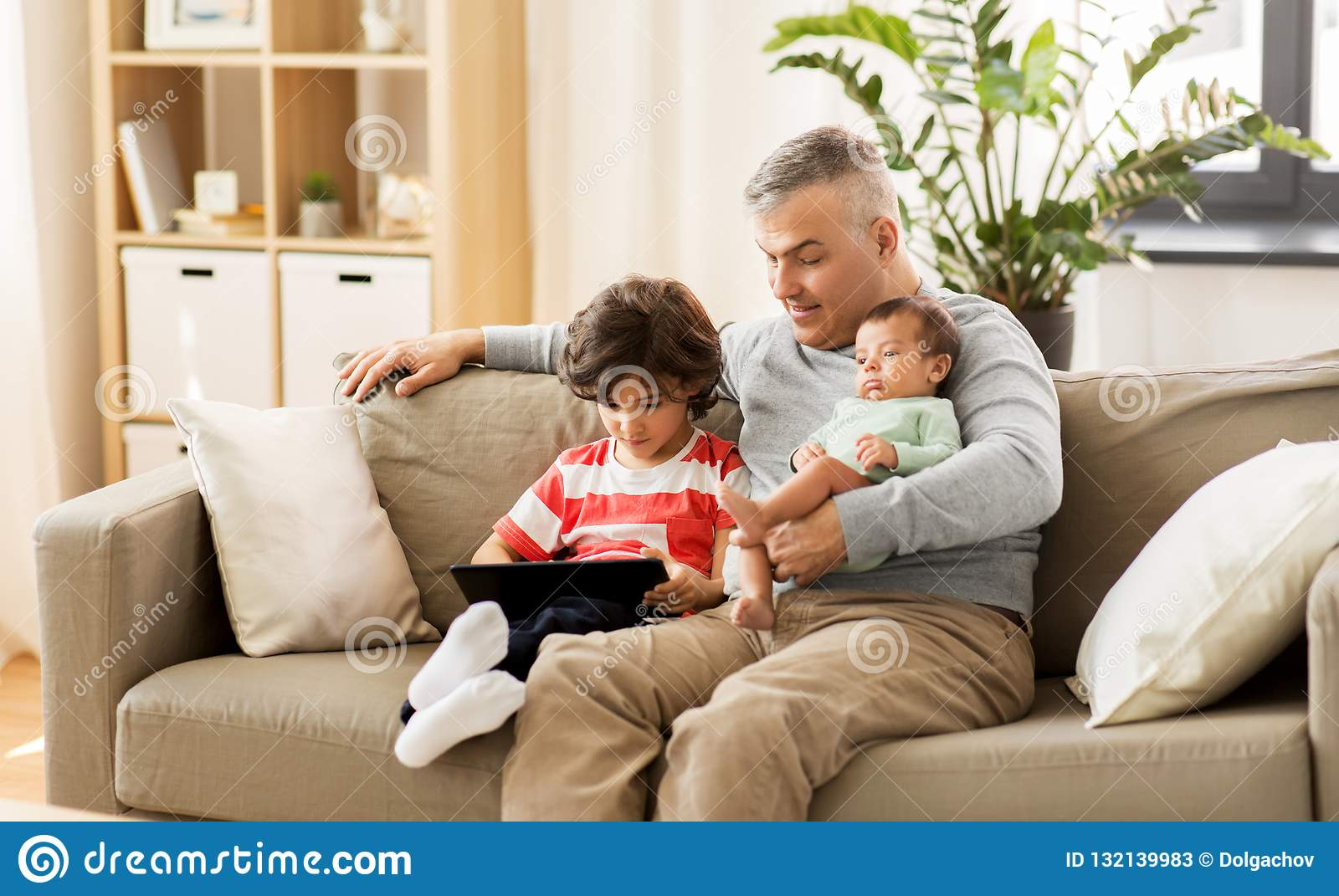 Happy Father With Preteen And Baby Son At Home Stock Image