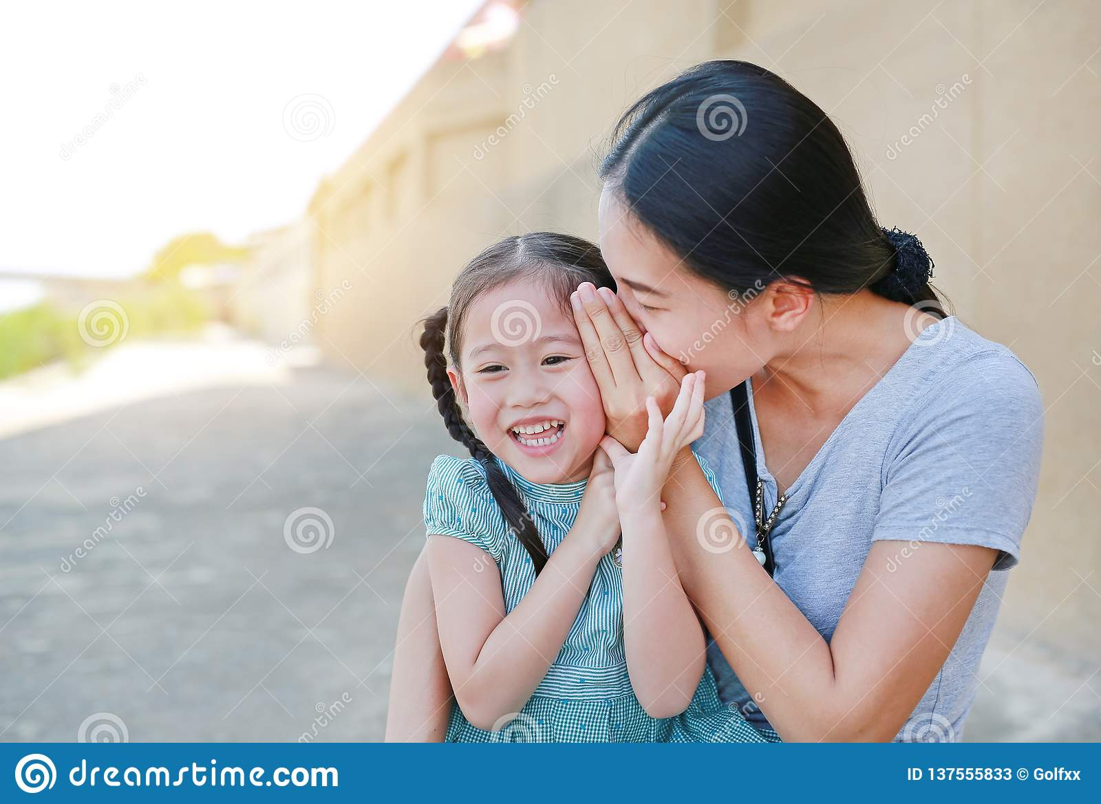Happy Mom Whispering A Something Secret To Her Little
