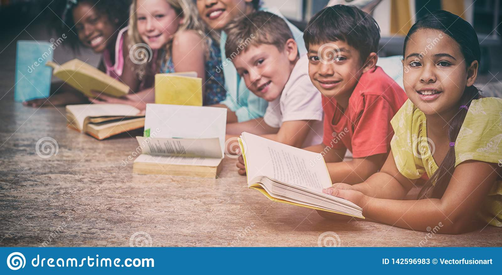 Happy Teacher With Children Lying Down While Reading Books