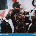 Happy Workers Decorating Christmas Tree In Office Stock