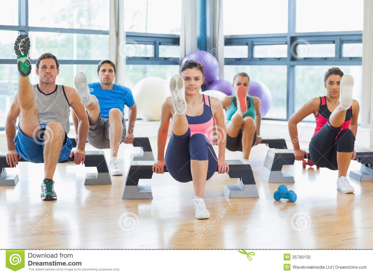 Instructor With Fitness Class Performing Step Aerobics