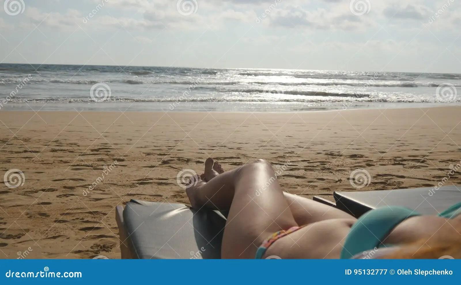 jeune femme se trouvant sur le lit pliant par la mer et le bronzage corps feminin