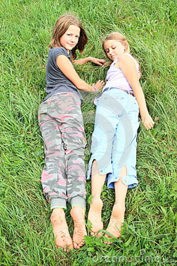 Dirty Soles Of Bare Feet Of Two Little Girls Smiling Kids Lying On Green Grass