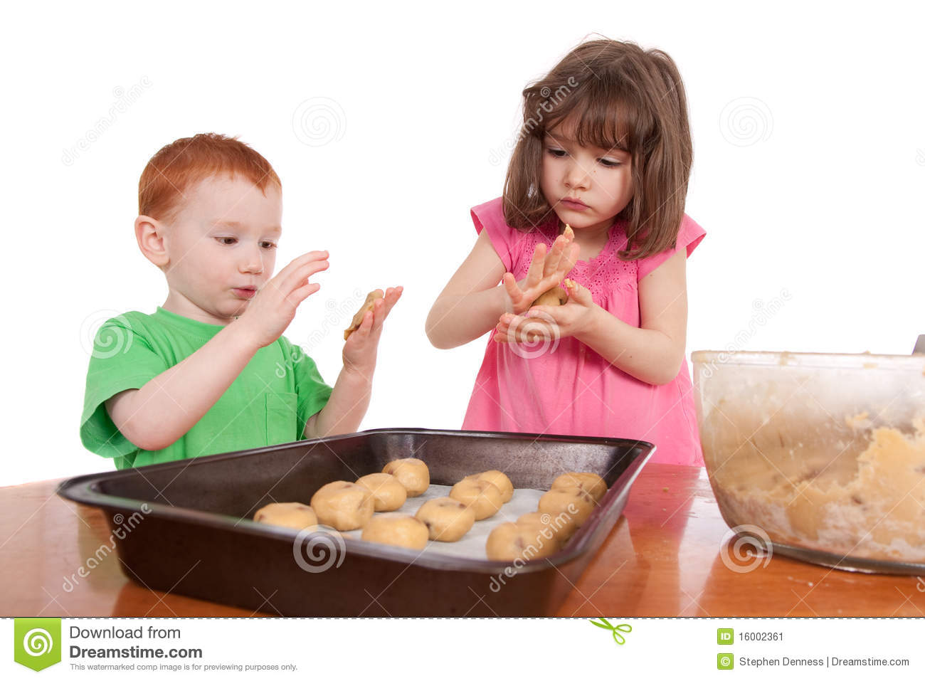Kids Rolling Out Chocolate Chip Cookies For Baking Stock