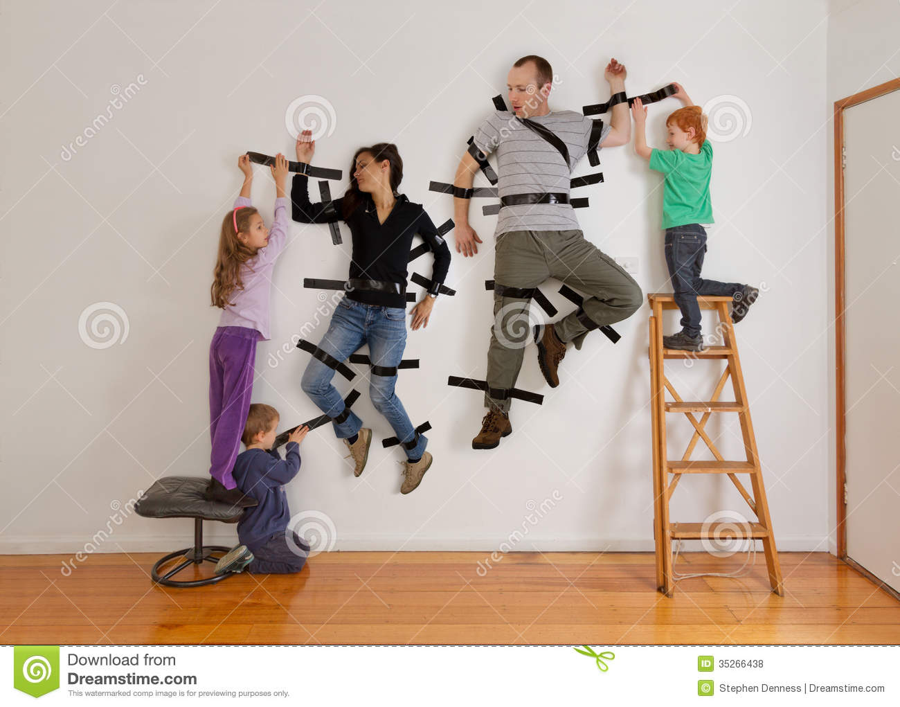 Kids Teamwork Taping Parents To Wall Stock Photo