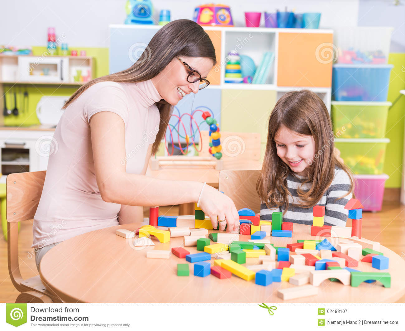 Kindergarten Teacher And Cute Smiling Girl Playing Stock