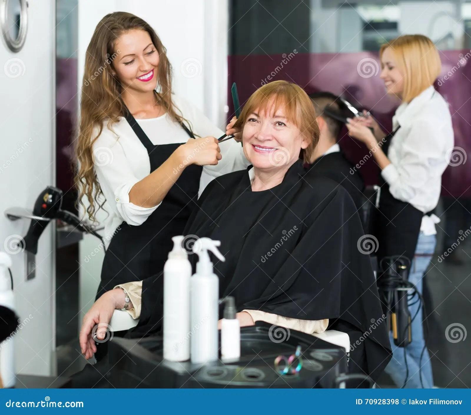 la femme mure coupe des cheveux avec le coiffeur photo stock image du coiffeur femme 70928398