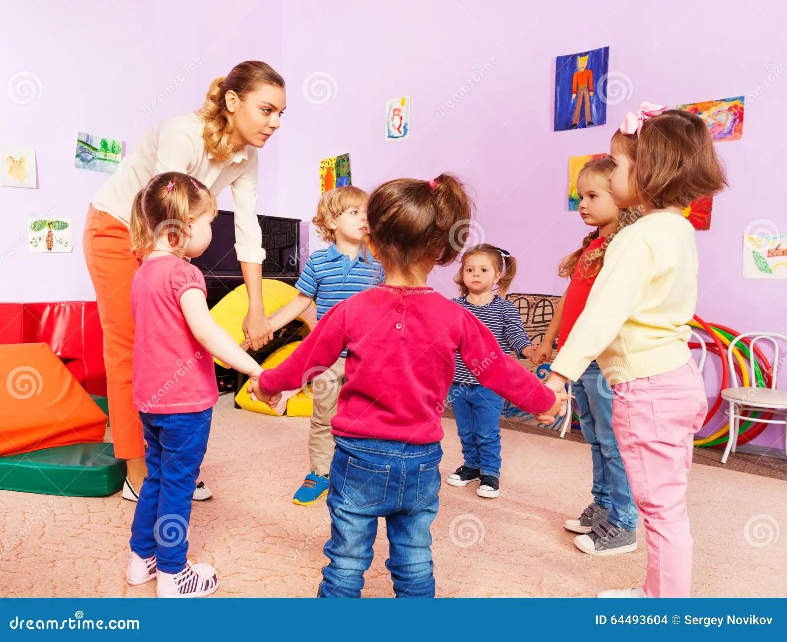 Lehrer Und Gruppe Kinder Im Kindergarten Stockfoto