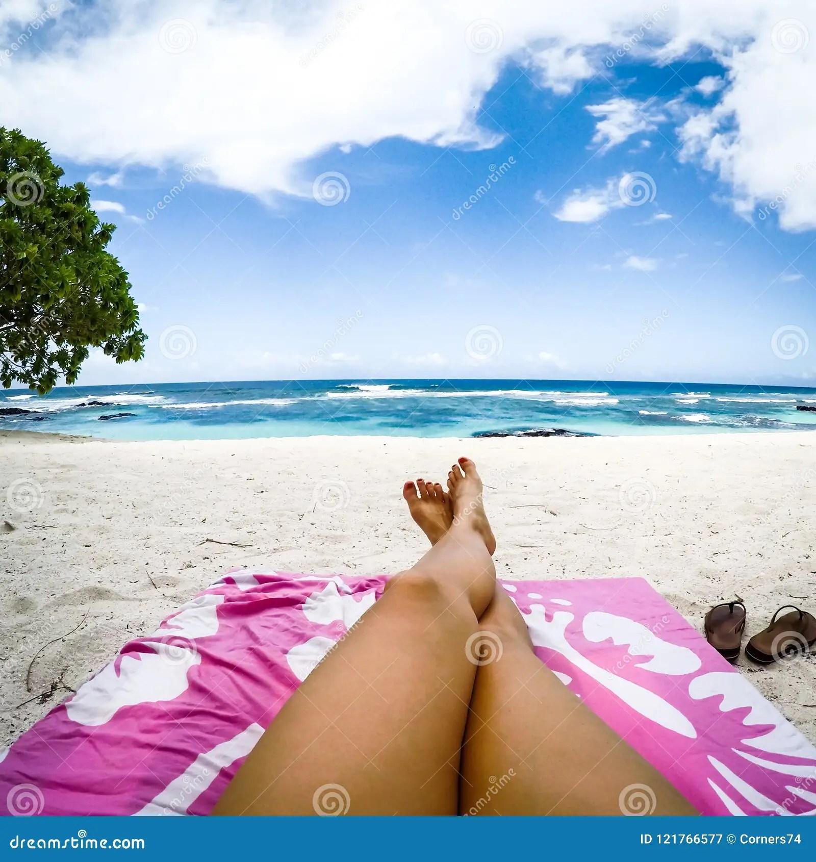 les jambes avec le faux jet se bronzent sur le canape du soleil sur la plage tropicale avec la serviette rose chez lefaga ile d upolu samoa occidental