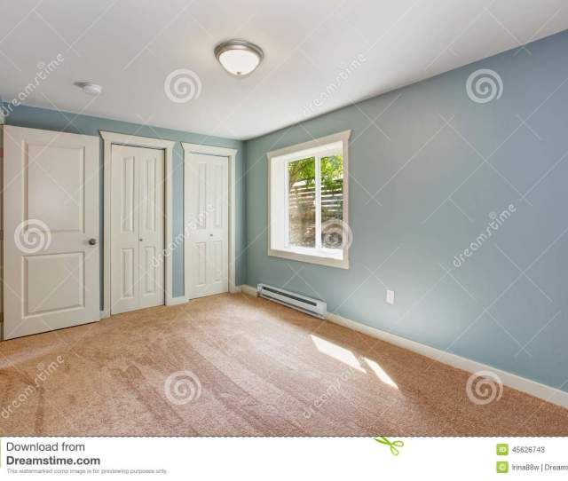 Empty Small Room With Light Blue Walls And Brown Carpet Floor Room Has Closets