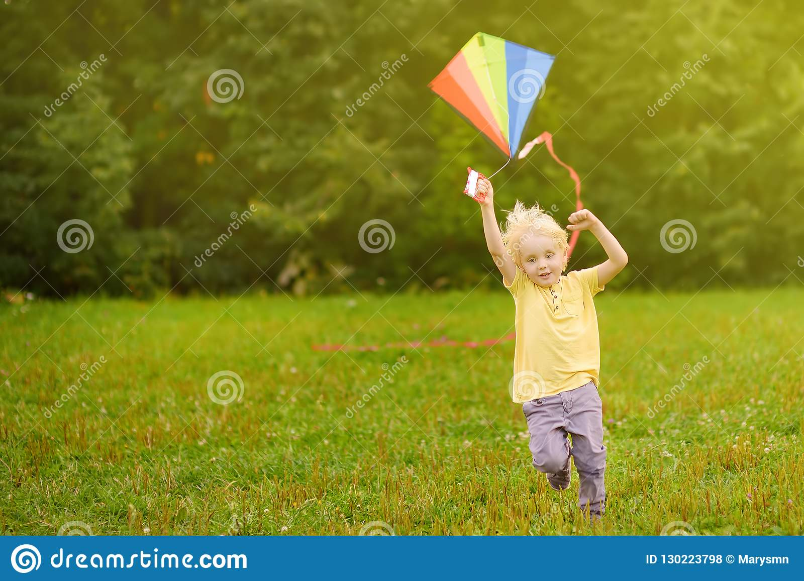 Little Boy On A Sunny Day Launches A Flying Kite Stock