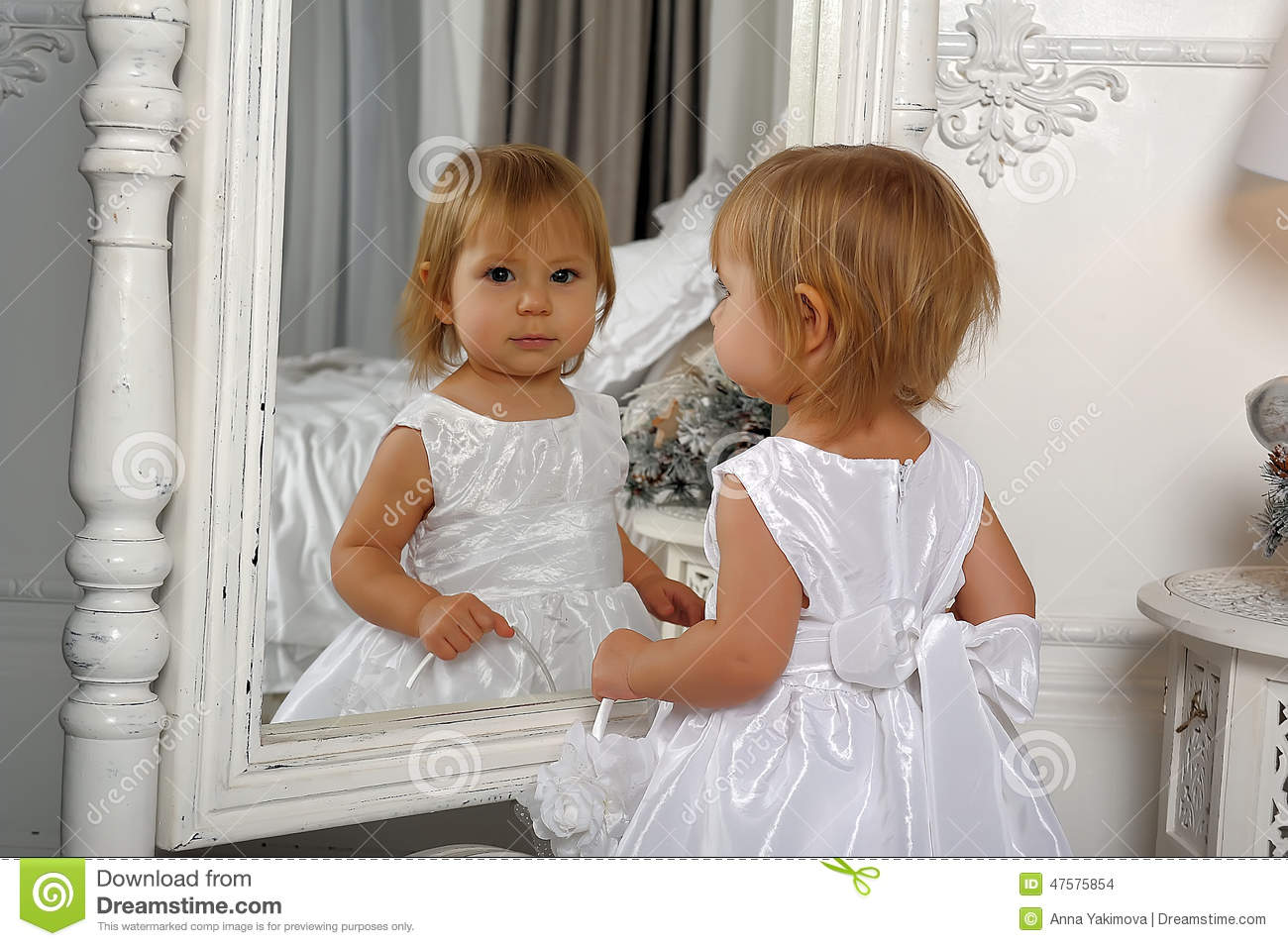 Little Girl Admires Her Reflection In Mirror Stock Photo