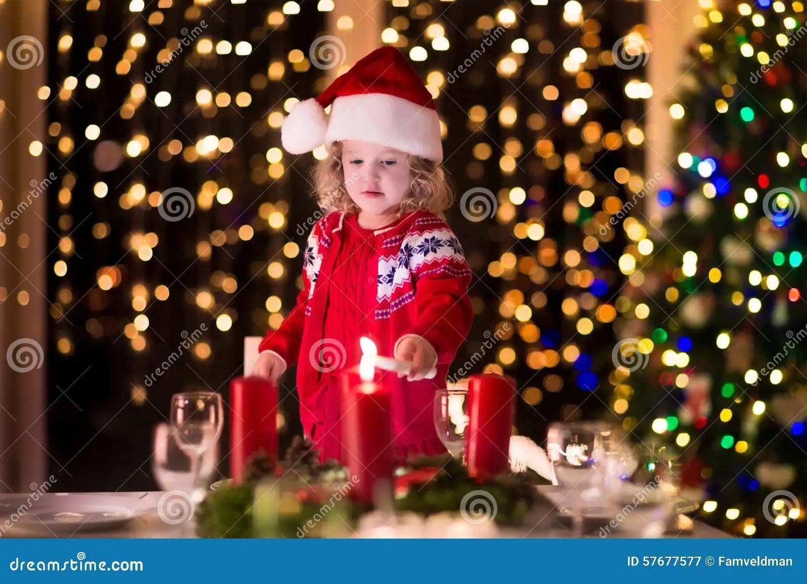 Little Girl Lighting Candles At Christmas Dinner Stock