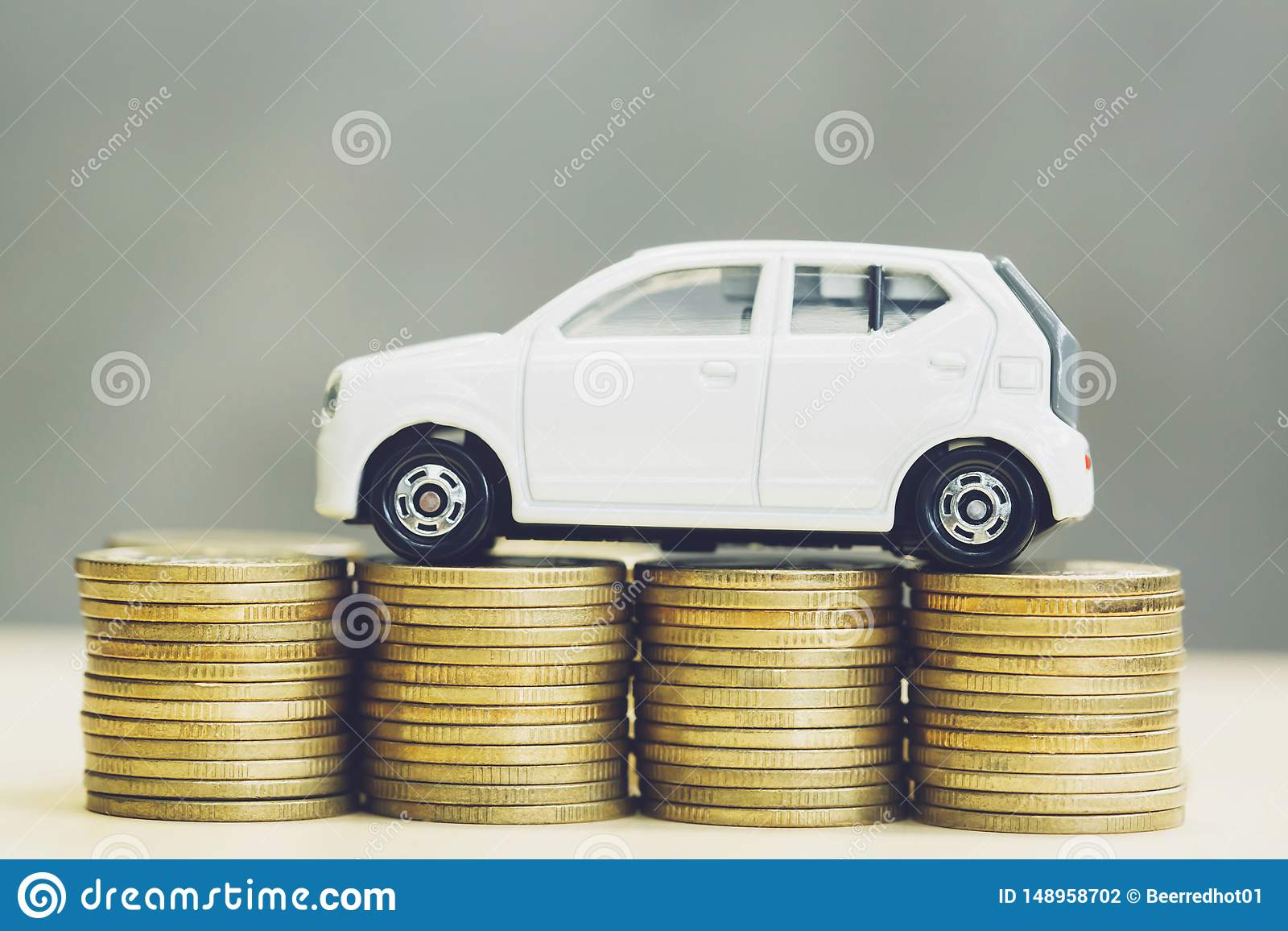 Little Toy White Car Over A Lot Of Money Stacked Coins