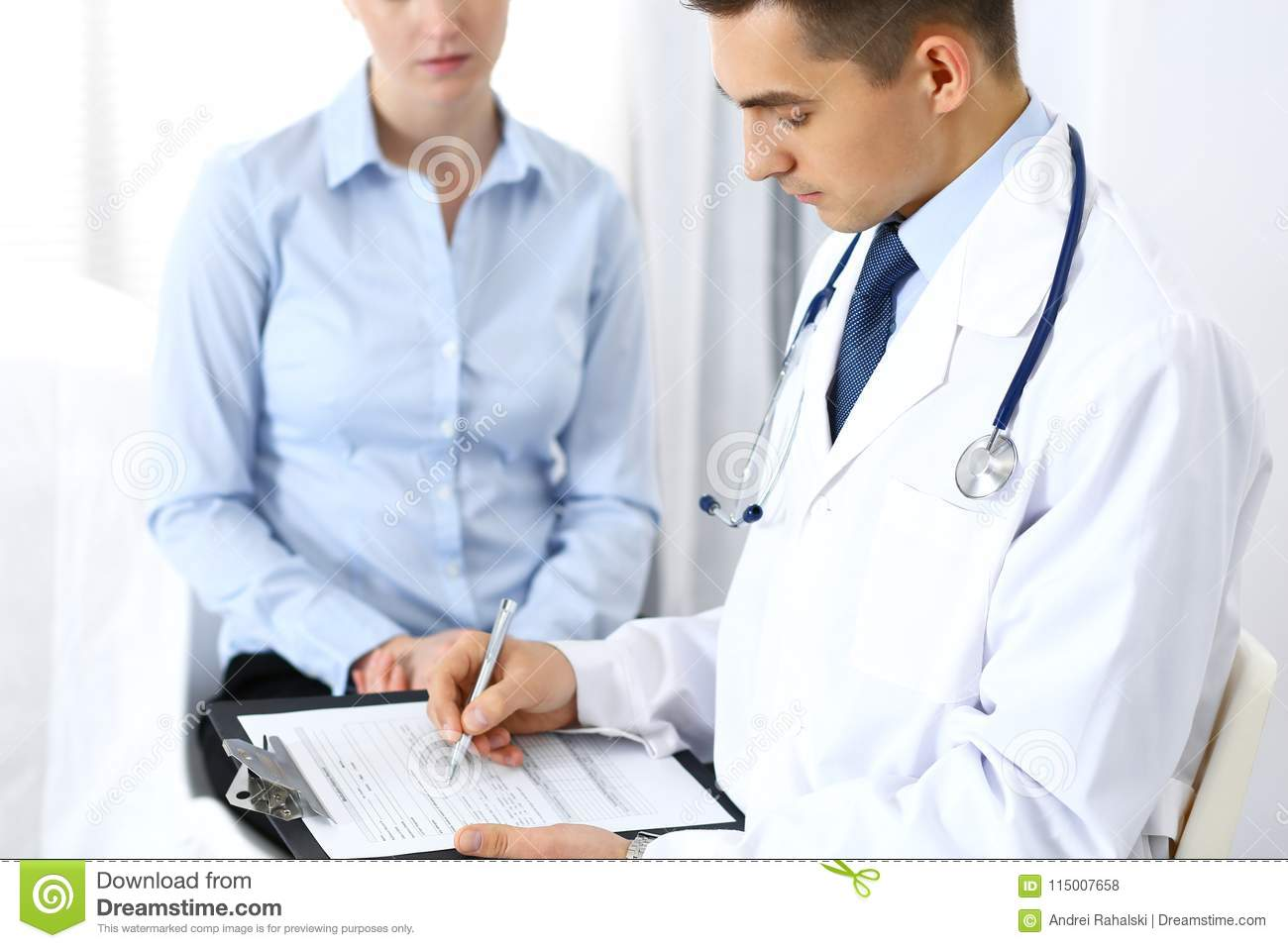 Male Doctor Holding Application Form While Consulting