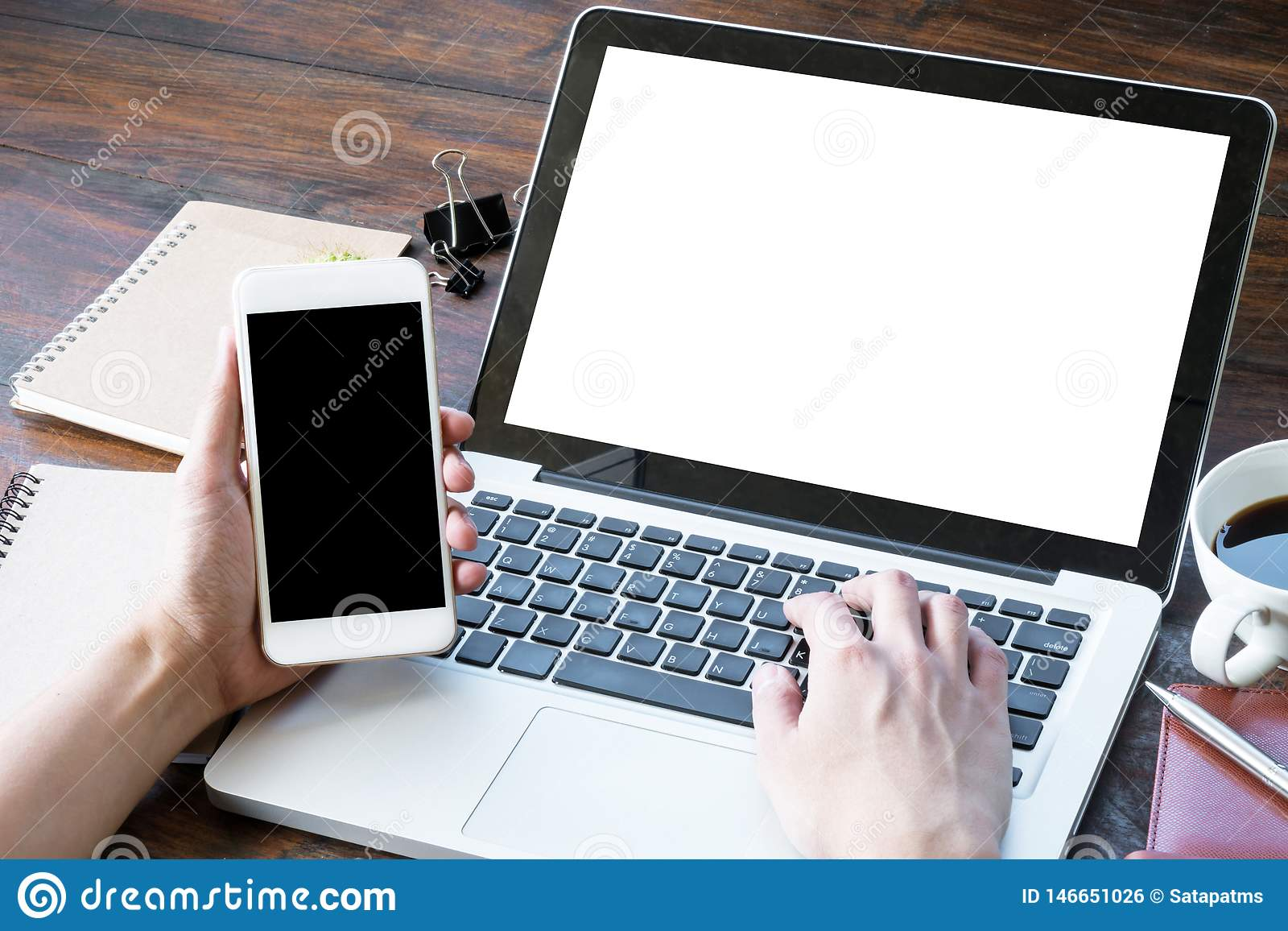 Man Is Holding Smartphone And Typing On Laptop Keyboard
