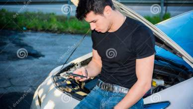 Man Trying To Repair Car And Seeking Help On Phone Stock