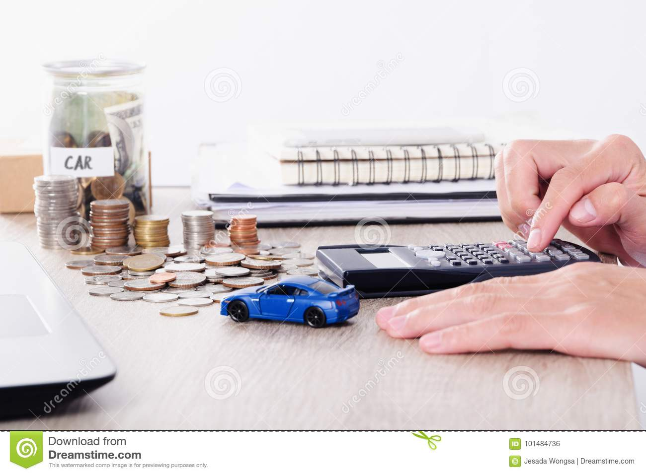Man Using Calculator With Car Toy And Coin Stack For