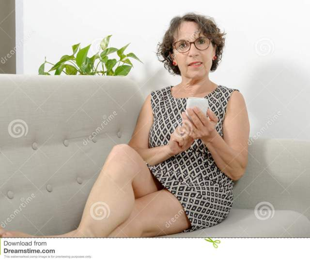 A Beautiful Mature Woman On The Sofa With A Phone