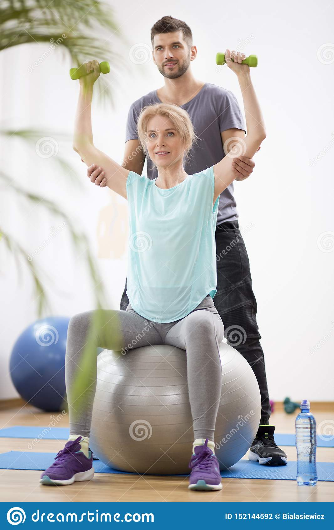 Middle Age Blond Woman Exercising On Gymnastic Ball During