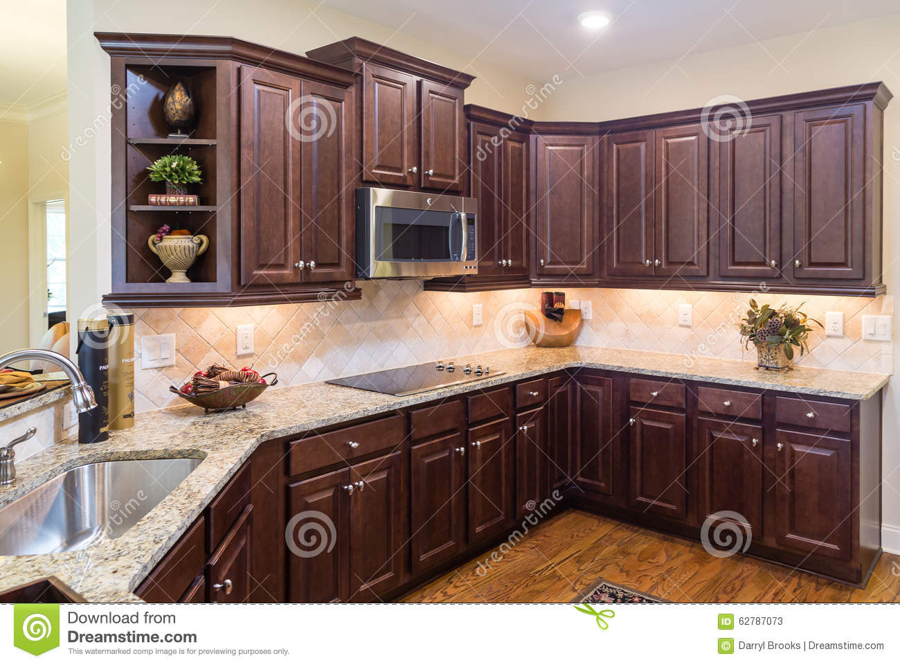 Modern Kitchen With Dark Cabinets And Wood Floor Stock