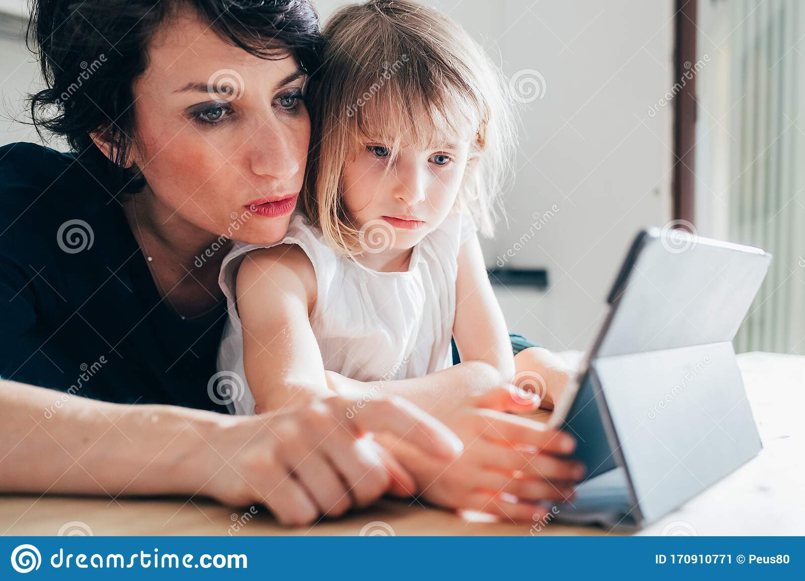 Mother And Daughter Indoor Using Tablet Stock Image