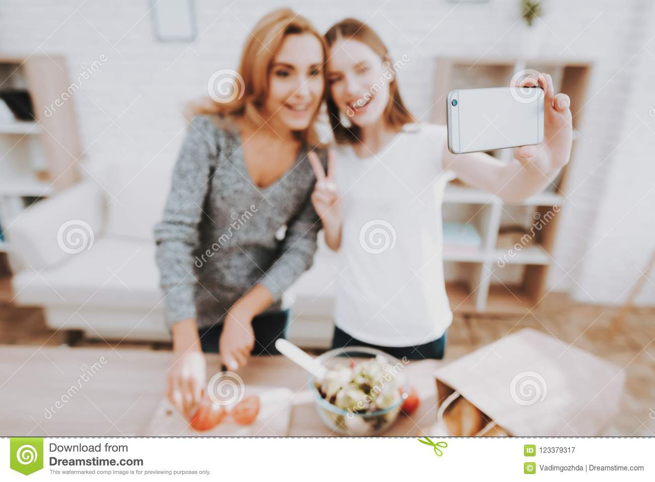 Mother And Daughter Taking Selfie In Kitchen Stock Image