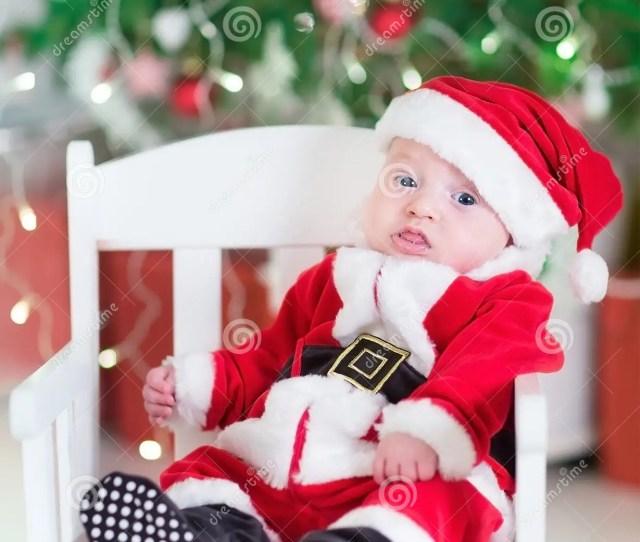 Newborn Baby Boy In Santa Outfit Sitting Under Chr