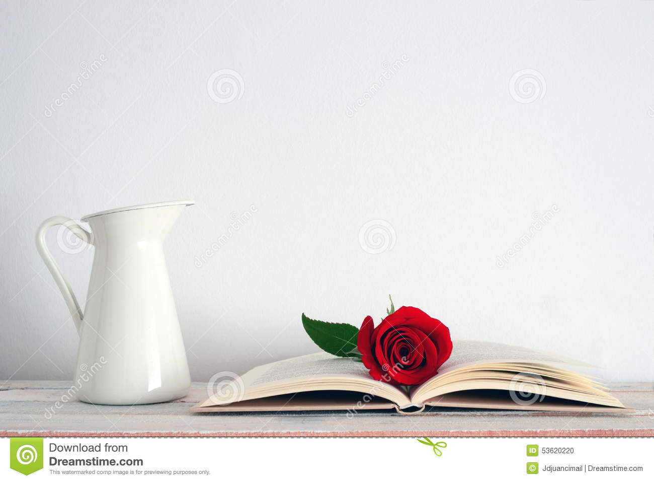 An Open Book With A Red Rose Flower On It Stock Photo