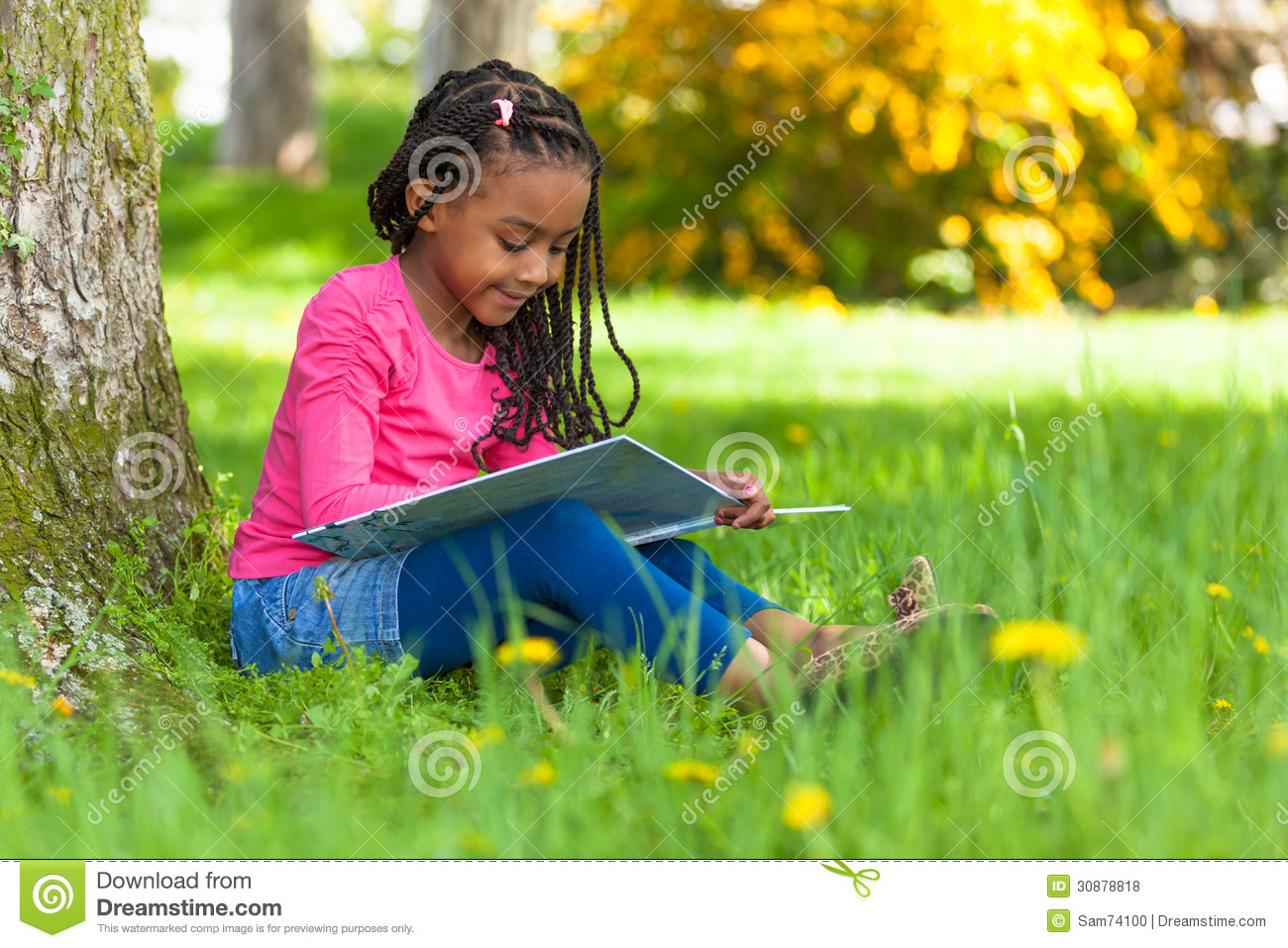 Outdoor Portrait Of A Cute Young Black Little Girl Reading
