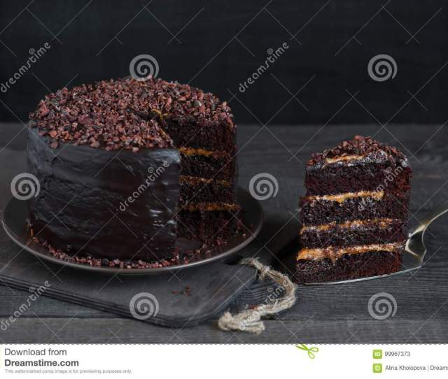 Piece Of Homemade Chocolate Cake With Caramel Cream On The Rough Table